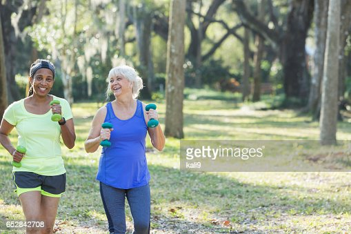 Senior women exercising in park run with hand weights : Bildbanksbilder