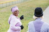 Senior women (60s) exercising in park on chilly autumn day.