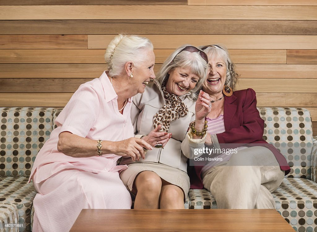 Senior women friends laughing on sofa : Stock-Foto