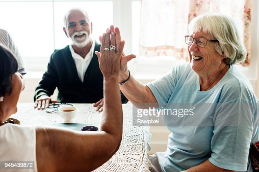Senior women giving each other high five : Stock Photo