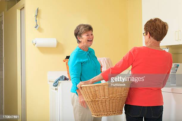 Senior women in a laundry room with basket