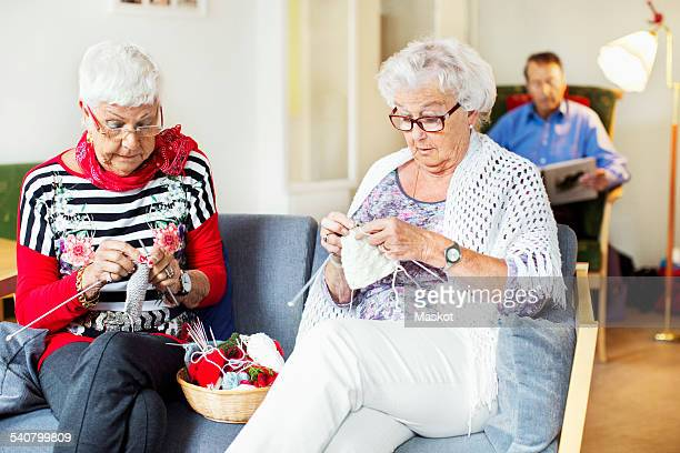 Senior women knitting while man reading book in background at nursing home