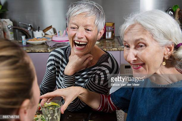 Senior women laughing at dinnerparty.