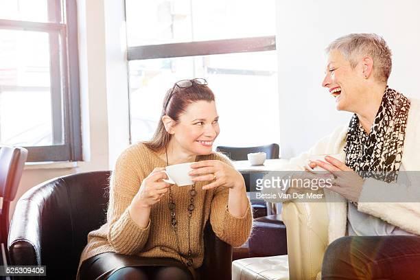 senior women laughing, drinking coffee in cafe.