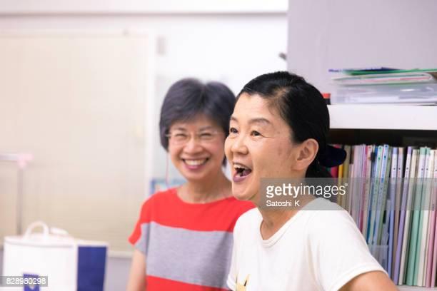 年配の女性は語学学校で英語を学ぶ