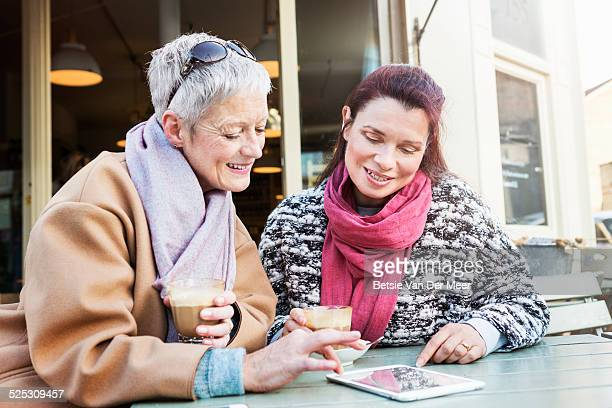 senior women looking at digital tablet in cafe.