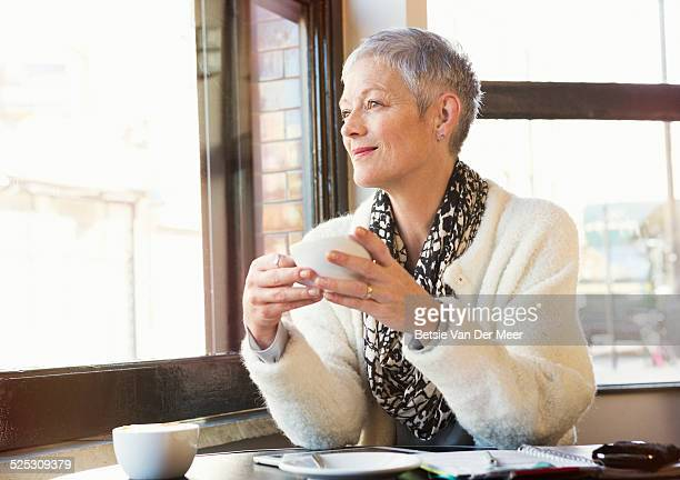 senior women looking out of window in cafe.