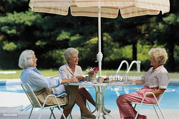 Senior women lounging poolside