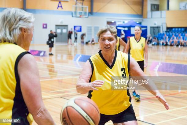 senior women playing basketball on court indoors