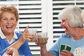 Senior women playing cards and enjoying tea