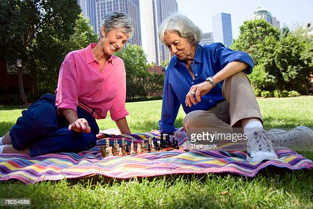 Senior women playing chess on blanket outdoors