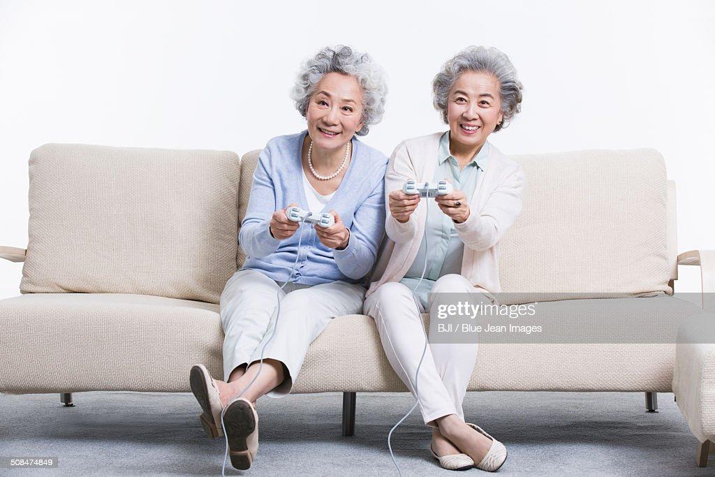 Senior women playing video game in living room