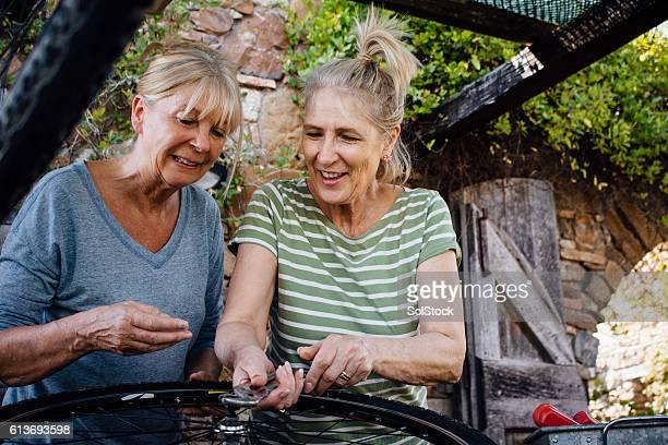 Senior Women Repairing a Bicycle Wheel