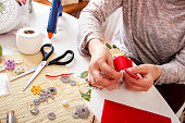 Senior women sews by hand and making heart shape ornament.
