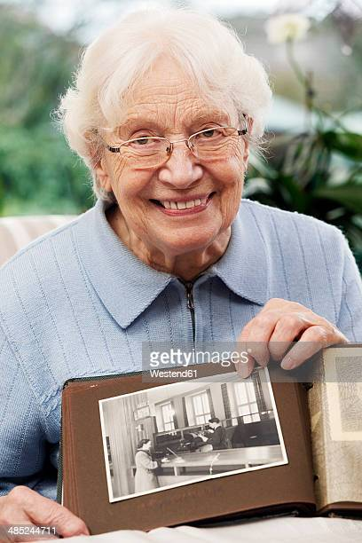 Senior women showing old photograph of herself