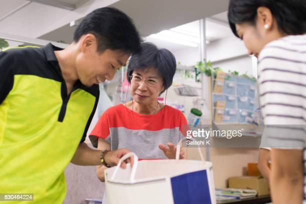 プレゼンテーションの前に紙袋に小道具を示す年配の女性