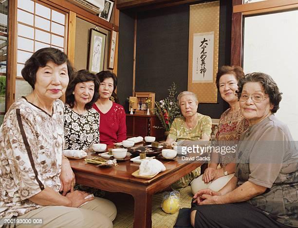 Senior women sitting around table, smiling, portrait