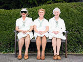 Senior Women Sitting in Row on a Bench in Front of a Hedge Wearing Bowling Sportswear