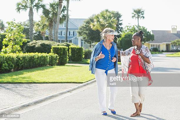 Senior women taking a walk on a sunny day, laughing