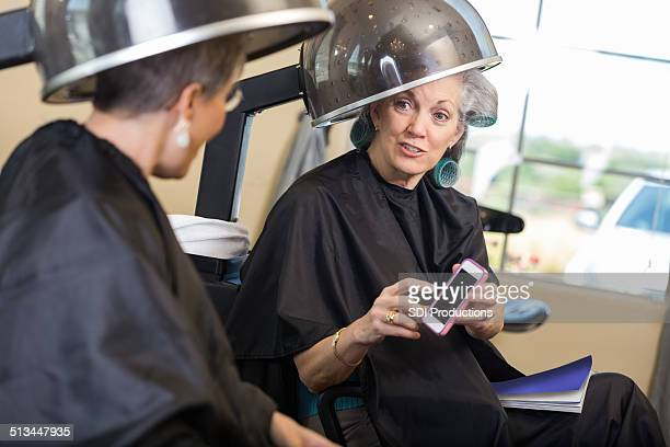 Senior women talking during beauty salon hair appointment
