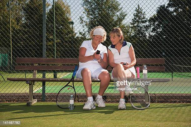 Senior women texting on tennis court