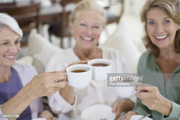 Ältere Frau beim Anstoßen Kaffee Tassen