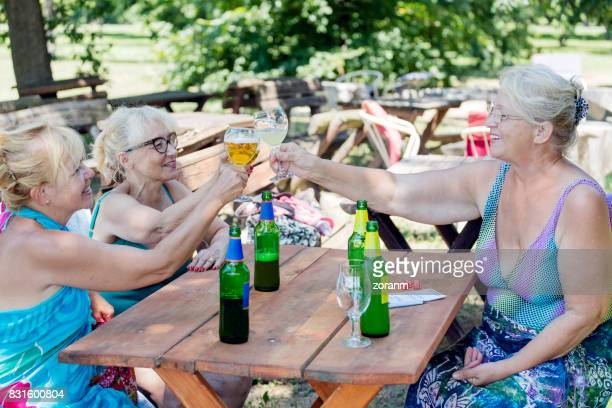 Senior women toasting with beer