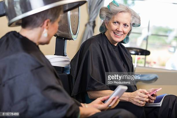 Senior women using smart phones during hair appointment at salon