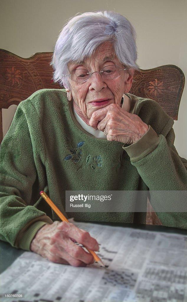 Senior women working on a crossword puzzle : Stock Photo