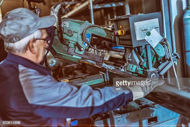 Senior Arbeiter Betrieb einer Stahl-Schneiden-Maschine