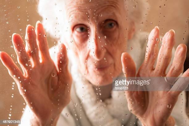 Seniors: 80-plus year old woman sadly looks through rainy window.