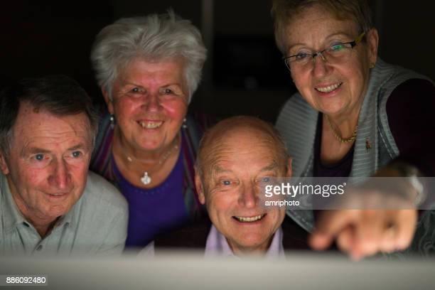 高齢者の家庭のコンピューターで一緒に幸せの年長の友人で