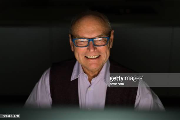 Seniors at Home - happy senior man looking at computer monitor