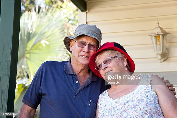 Seniors Couple in front of house home