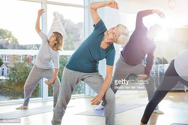 seniors exercising in yoga class indoors.