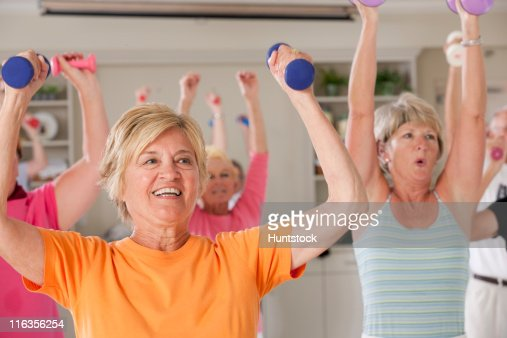 Seniors exercising with dumbbells in a health club : Foto de stock
