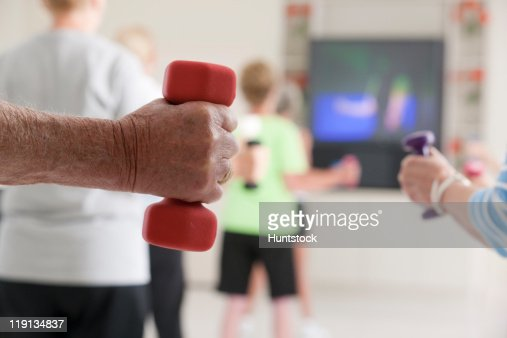Seniors exercising with dumbbells in a health club : Stock Photo