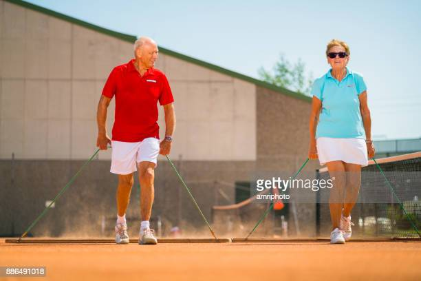 Seniors - happy 70 years old senior coupla at tennis court