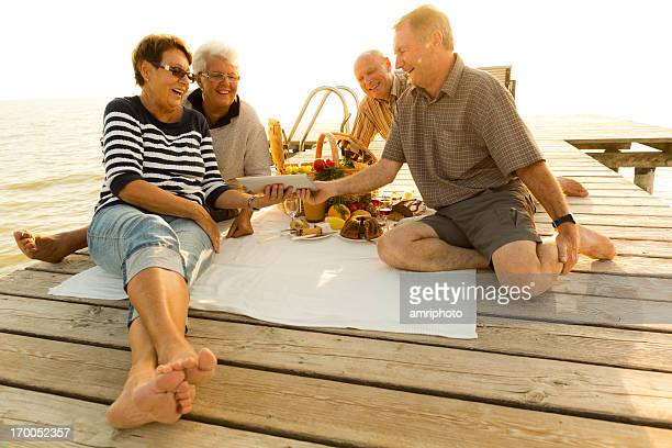 seniors having fun during picnic on jetty