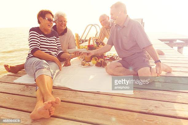 seniors having fun viewing tablet on jetty