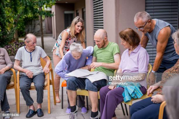 Seniors Having Group Therapy Outside In The Retirement Home
