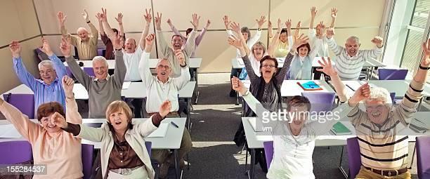 Seniors in the community center raising hands