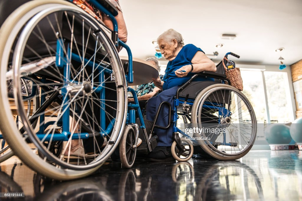 Seniors On The Wheelchair In The Nursing Home Waiting For The Therapy In The Gym Class : Stock-Foto