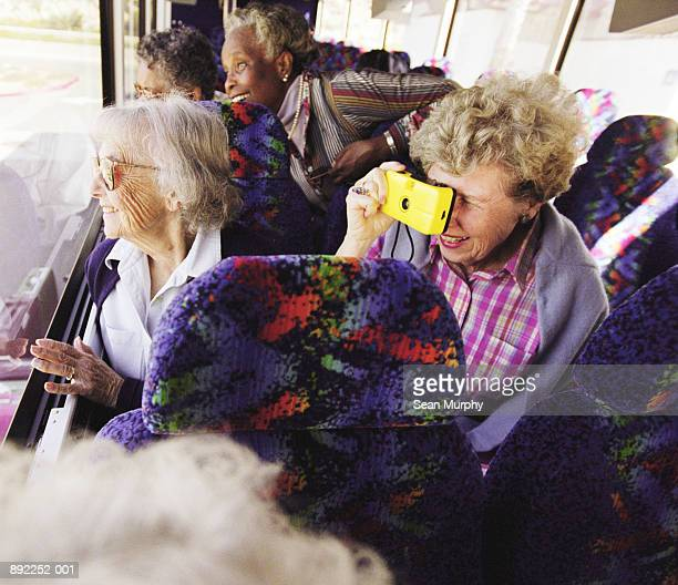 Seniors on tour bus looking out window, woman taking picture