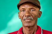 Real Cuban people and feelings, portrait of sad senior african american man looking at camera. Worried old latino grandfather with mustache and hat from Havana, Cuba