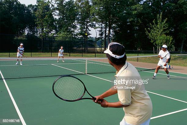 Seniors playing doubles tennis