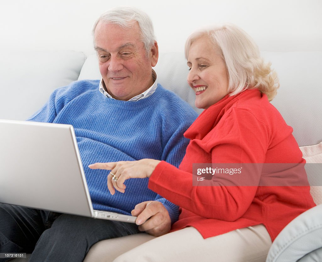 Seniors surfing in internet with a laptop : Stock Photo