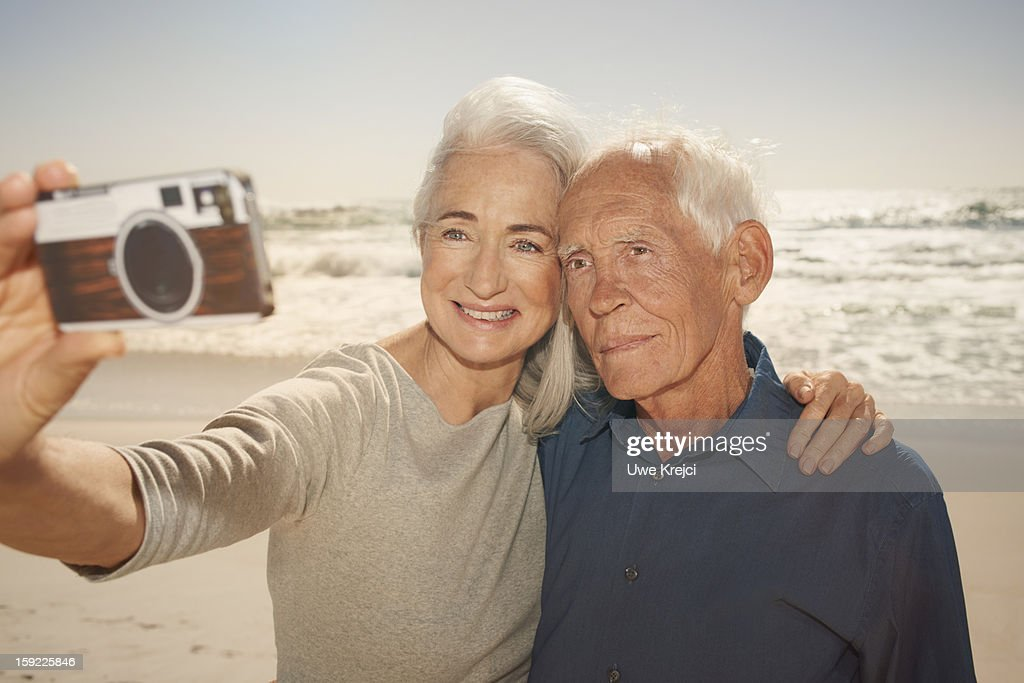 Seniors taking self-portrait with smart phone : Stock Photo