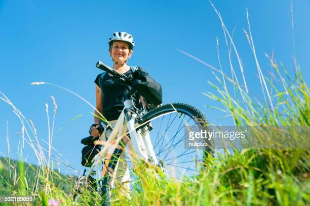 Senioren stehen mit Mountainbikes auf Hügel