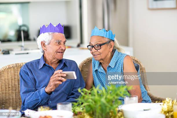Seniors with party hats and mobile phone